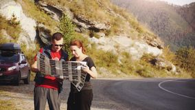 Tourists are guided by the terrain with a map. Young beautiful couple stand in amazing picturesque place amidst the stock video