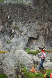 Tourists on a halt under the sheer cliff Royalty Free Stock Photography