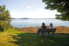Tourists at harbor resort. A view of female tourists talking together as they sit on a park bench with a pretty view of the water at Bar Harbor, Maine Royalty Free Stock Photography