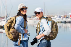 Tourists at harbour. Young female tourists at the harbour looking back Royalty Free Stock Photo