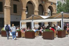 Tourists have fun at a terrace in the city of Inca, Mallorca, Spain. People relax at a sunny outdoor terrace in the city center of Inca, isle of Mallorca,Spain royalty free stock images