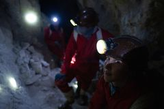 Tourists have a rest inside the cooperative mine. Located in the mountain of Cerro Rico near the city of Potosi, Bolivia. Image has high level of noise stock images