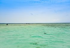View of fisherman tourists walking on the shallow water of calm ocean stock photography