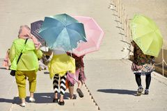 Tourists hide under umbrellas from the sun while traveling stock photography