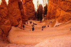 Tourists hike down sandstone ledges Royalty Free Stock Photo