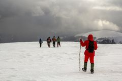 Tourists hikers in winter snow covered mountains and dramatic cl stock photo