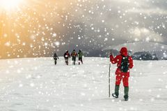 Tourists hikers in winter snow covered mountains and dramatic cl stock image