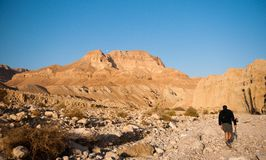 Tourists hiking in dead sea mountains Stock Photo