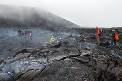 Tourists hiking on hot and steaming lava field eruption Tolbachik Volcano on Kamchatka. Russia Royalty Free Stock Images
