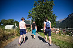 Tourists hiking in Italian Alps. Italian Alps hiking - three tourists walking along a narrow asphalt road through a village of Alpe di Siusi Stock Photos