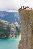 Tourists hiking at the Preikestolen cliff in lysefjorden Norway Stock Photo