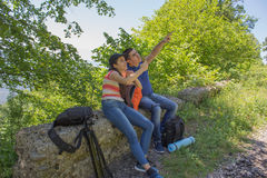 Tourists hitching a ride. Active hikers. Travelers travel on the road in mountains go trekking together. Trekking together royalty free stock images