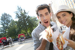 Tourists with hot dog in new york. Tourists in New York city eating hot dogs stock image