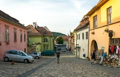 Tourists and houses on streets of the medieval town of Sighisoara, Romania. Ancient buildings and street cafes stock image