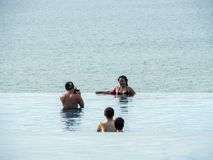 Tourists in an infinity pool with ocean background stock photo