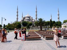 Tourists in Istanbul. Tourists take pictures and enjoy the sunny weather near the famous Blue Mosque in Istanbul, Turkey. Photograph taken on June, 2014 Stock Photography