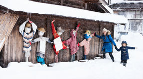 Tourists in Japan at winter. Family of mother and daughter with funny scarecrows at historic Japanese village Shirakawa-go at winter, one of Japan's UNESCO world Royalty Free Stock Photo