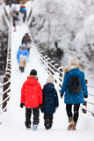 Tourists in Japan at winter. Family of mother and kids crossing the bridge over Shogawa river at historic Japanese village Shirakawa-go at winter, one of Japan's Stock Photo