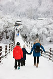 Tourists in Japan at winter. Family of mother and kids crossing the bridge over Shogawa river at historic Japanese village Shirakawa-go at winter, one of Japan's Royalty Free Stock Photo