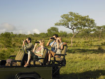 Tourists In Jeep Looking Through Binoculars Stock Photography