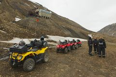 Tourists join the excursion on off-road vehicles near Longyearbyen, Norway. LONGYEARBYEN, NORWAY - SEPTEMBER 01, 2011: Unidentified tourists join the excursion Royalty Free Stock Photo
