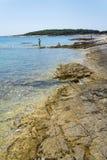 Tourists on Kamenjak peninsula beach by the Adriatic Sea in Premantura, Croatia. PREMANTURA, CROATIA - JULY 28: Tourists on Kamenjak peninsula beach by the stock photos