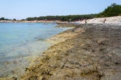 Tourists on Kamenjak peninsula beach by the Adriatic Sea in Premantura, Croatia. PREMANTURA, CROATIA - JULY 28: Tourists on Kamenjak peninsula beach by the stock photo