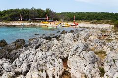 Tourists on Kamenjak peninsula beach by the Adriatic Sea in Premantura, Croatia. PREMANTURA, CROATIA - JULY 28: Tourists on Kamenjak peninsula beach by the royalty free stock image