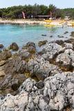 Tourists on Kamenjak peninsula beach by the Adriatic Sea in Premantura, Croatia. PREMANTURA, CROATIA - JULY 28: Tourists on Kamenjak peninsula beach by the stock images
