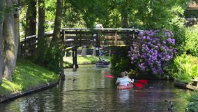 Tourists kayaking on the canal of the village of Giethoorn stock video