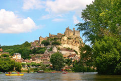 Tourists kayaking on river Dordogne in France. Tourists kayaking on river Dordogne with Château de Beynac in the background as seen in Beynac-et-Cazenac royalty free stock photo