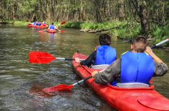 Tourists kayaking on river. In the forest stock photos