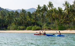 Tourists kayaking on sunny tropical beach with palm trees. Koh Chang, Thailand MARCH 28, 2015; Tourists kayaking on sunny tropical beach with palm trees Royalty Free Stock Photos