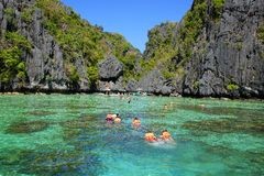 Tourists in lifejackets swimming at lagoon. El Nido, Philippines royalty free stock image