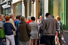 Tourists listen with attention their guide on the street of Antwerp Royalty Free Stock Images