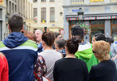 Tourists listening to their guide on Grand Place. Stock Photo