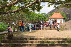 Tourists and local people crowd near entrance to Dambulla Golden. DAMBULLA, SRI LANKA -  NOV 2016: Tourists and local people crowd near entrance to Golden cave Stock Photo