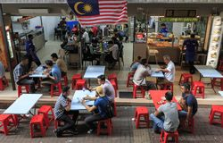 Tourists and local people eating in a Malaysian restaurant in Kuala Lumpur. Kuala Lumpur, Malaysia: January 24, 2018: Tourists and local people eating in a stock photos