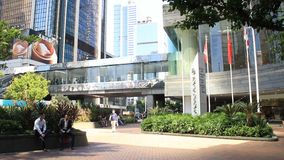 City life and modern office buildings in Hong Kong. Tourists and local residents walking along the street in commercial area over modern office buildings stock video