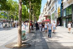 Tourists and locals at the Champs-Elysees in central Paris. PARIS,FRANCE - JULY 29,2017 : The Champs-Elysees next to the Lido Cabaret in central Paris on a sunny stock photography