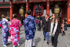 Tourists and locals dressed with kimonos walking in Senso-ji temple looking at the giant lantern stock photos