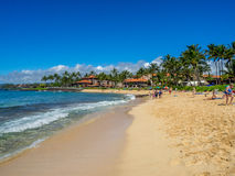 Tourists and locals enjoy Poipu Beach, Kauai. KAUAI, USA - MAR 3: Tourists and locals enjoy Poipu Beach on March 3, 2017 on Kauai, Hawaii. Poipu Beach is one of royalty free stock photography
