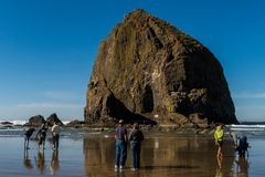 Tourists and locals enjoying the beach with Haystack Rock in the background at Cannon beach, Oregon, USA. royalty free stock image
