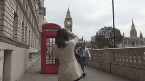 Tourists on London streets make photos with traditional red telephone booth.  stock video footage