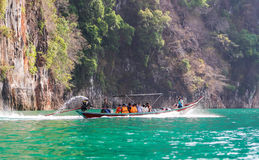 Tourists on long trail boat with speed on green water surface. Suratthani, Thailand - April 14, 2015 : Travelling tourists travel by long trail boat with speed Royalty Free Stock Image