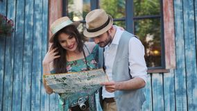 Tourists look at the map of the city. couple travelers. Couple of tourists are exploring the map in travel. a young woman and a man walk around the city on a stock footage