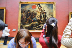 Tourists look at the paintings of Eugene Delacroix at the Louvre Museum (Musee du Louvre) Stock Photography