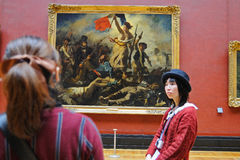 Tourists look at the paintings of Eugene Delacroix at the Louvre Museum (Musee du Louvre) Royalty Free Stock Photos