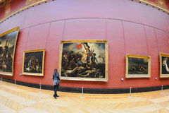 Tourists look at the paintings of Eugene Delacroix at the Louvre Museum Royalty Free Stock Image
