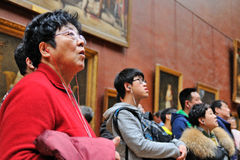 Tourists look at the paintings at the Louvre Museum Royalty Free Stock Image